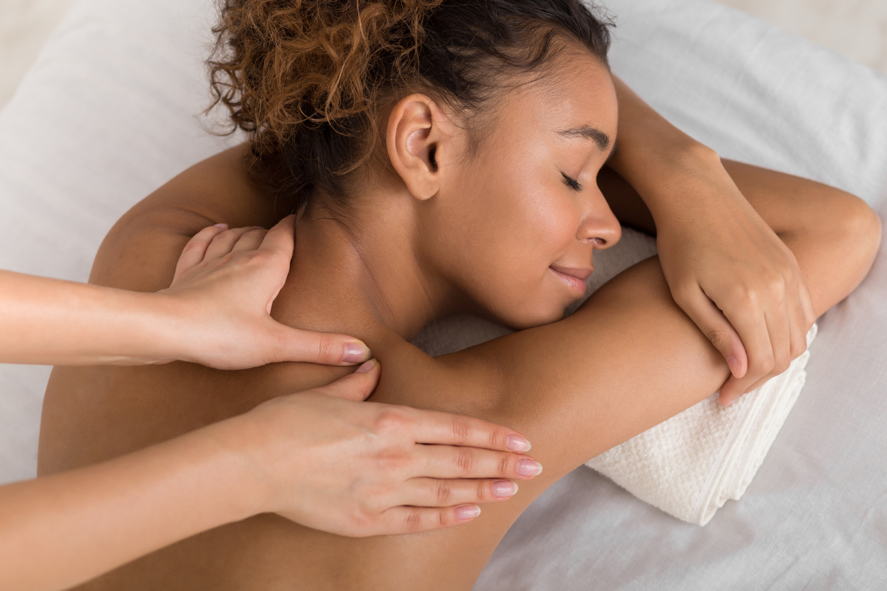 African-american woman enjoying shoulder massage in spa